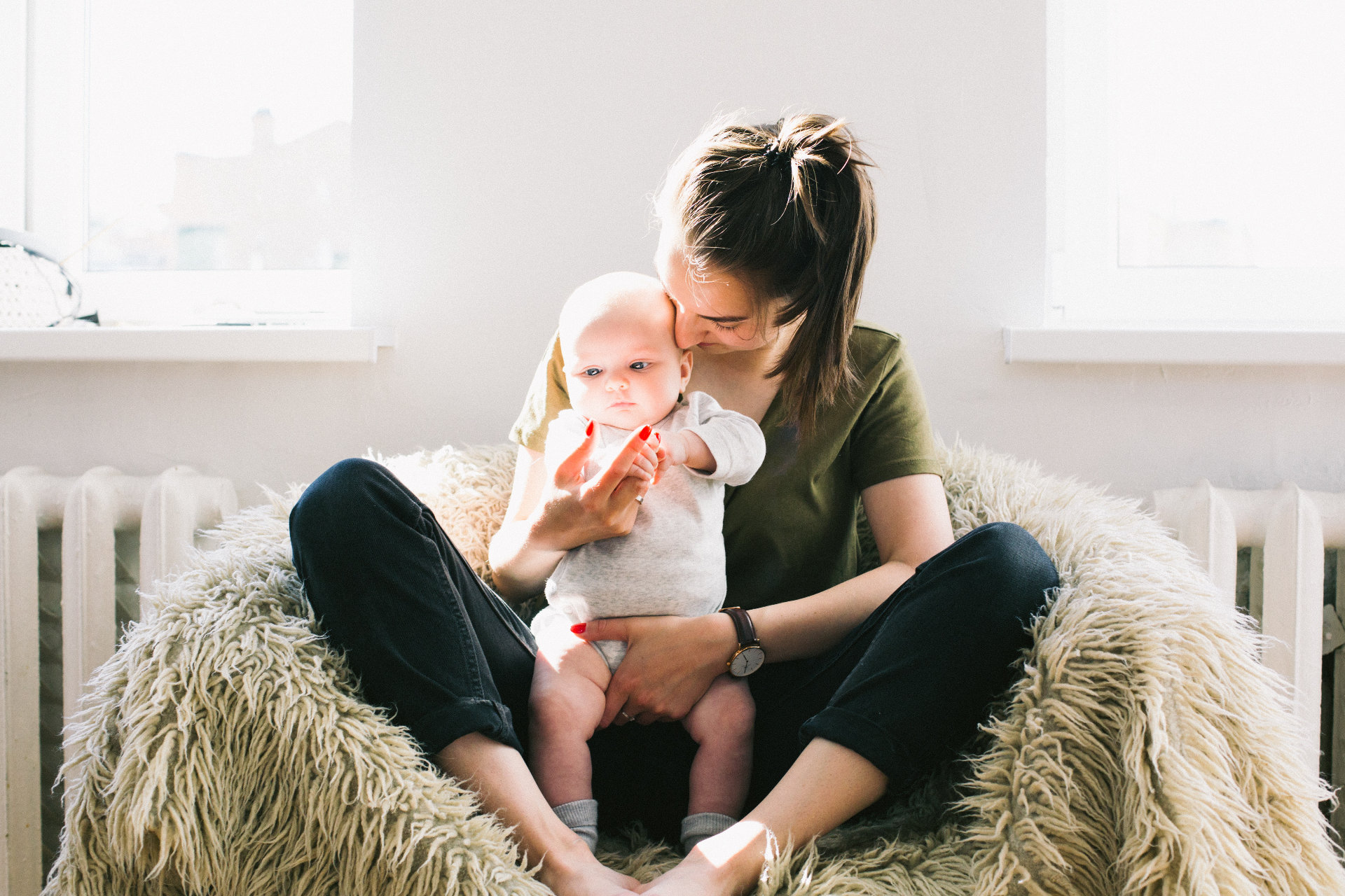 woman-holding-baby-while-sitting-on-fur-bean-bag-698878